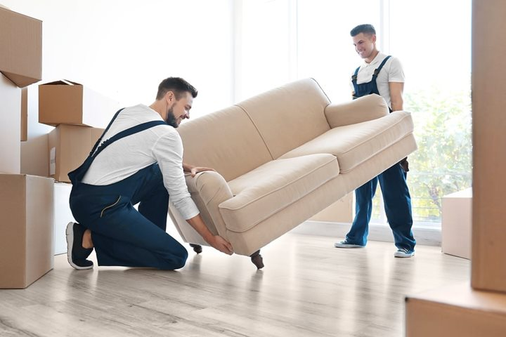 two men carrying a sofa