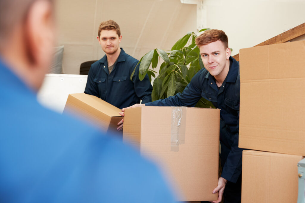 Removal Company Workers Unloading Furniture And Boxes From Truck Into New Home On Moving Day
